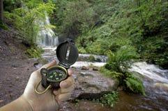 Mann mit Kompaß nahe Wasserfall stockfotos