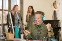 Mann mit Kopfhörern laut singend und Belästigungskollegen stockfoto