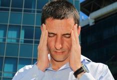 Mann mit Kopfschmerzen Betonter Geschäftsmann, der unter Kopfschmerzen leidet Stockbild