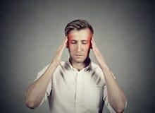 Mann mit Kopfschmerzen sehr intensiv sich konzentrieren denkend lizenzfreies stockbild