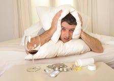 Mann mit Kopfschmerzen und Kater im Bett mit Tabletten lizenzfreie stockbilder