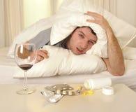 Mann mit Kopfschmerzen und Kater im Bett mit Tabletten lizenzfreie stockfotografie