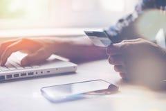 Mann mit Kreditkarte und Smartphone unter Verwendung des Laptops Internet-Zahlung Stockbild