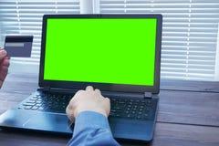Mann mit Kreditplastikkarte schreibend auf Laptop Stockfoto