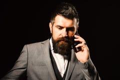 Mann mit langem Bart hält Handy Geschäft und Telefongesprächskonzept Macho im Gesellschaftsanzug Stockbild