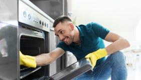 Mann mit Lappenreinigung innerhalb der Küche des Ofens zu Hause Stockbilder