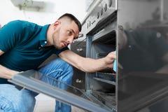 Mann mit Lappenreinigung innerhalb der Küche des Ofens zu Hause Lizenzfreie Stockbilder