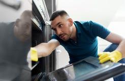 Mann mit Lappenreinigung innerhalb der Küche des Ofens zu Hause Stockfoto