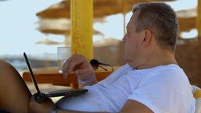 Mann mit Laptop auf dem Strand