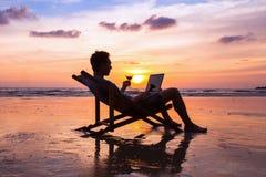 Mann mit Laptop auf Sonnenuntergangstrand stockfotos