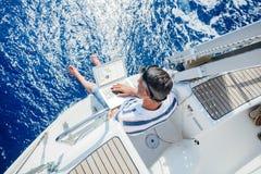 Mann mit Laptop-Computer auf Segelboot stockbild