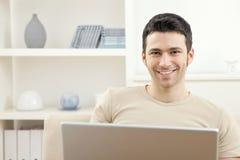 Mann mit Laptop-Computer zu Hause Lizenzfreies Stockfoto