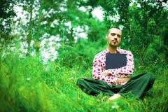 Mann mit Laptop im Garten Stockfoto
