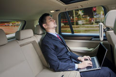 Mann mit Laptop sleepin in einem Auto stockfotografie