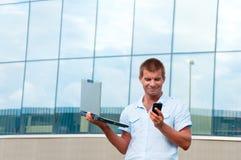 Mann mit Laptop und Handy vor modernem Geschäftsgebäude Stockbild