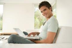 Mann mit Laptop zu Hause lächelnd Lizenzfreie Stockbilder