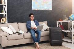 Mann mit Laptopplanungsferien, Anmeldungskarten stockfoto