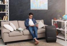 Mann mit Laptopplanungsferien, Anmeldungskarten lizenzfreies stockbild
