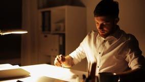 Mann mit Laptopvollendenarbeit im Nachtbüro stock video
