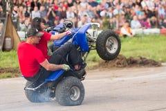 Mann mit Mädchen fährt auf die Hinterräder auf einem Viererkabelfahrrad Lizenzfreie Stockbilder