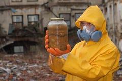 Mann mit Maske und Schutzkleidung erforscht Gefahrenglas r Lizenzfreies Stockbild