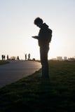Mann mit Mobiltelefon im Park Stockbild