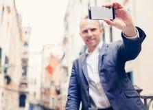 Mann mit modernem Smartphone machen ein selfie Foto auf Venedig-Straße Lizenzfreie Stockfotografie