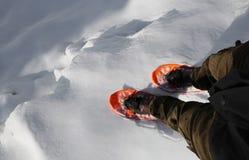 Mann mit orange Schneeschuhen geht nahe einer tiefen Gletscherspalte in hohem mou lizenzfreie stockbilder