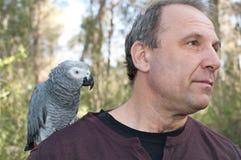 Mann mit Papageien. Stockfoto