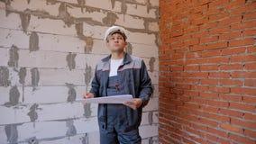 Mann mit Papieren Raum im Gebäude im Bau erforschend stock video footage