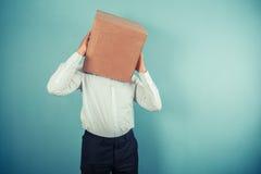 Mann mit Pappschachtel auf seinem Kopf Lizenzfreies Stockbild