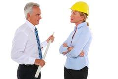 Mann mit Plan und Frauenarchitekt mit hartem Hut Stockfotos