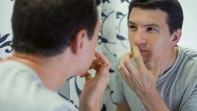 Mann mit Problem-Haut vor dem Spiegel stock video footage
