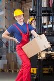 Mann mit Rückenschmerzen in der Fabrik Stockfotos