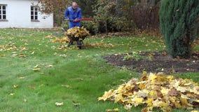 Mann mit Rakerrührstangenblatt und Lastskarren mit Herbstlaub im Hausyard 4K stock video footage