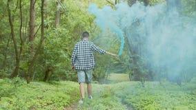 Mann mit Rauchbombe gehend durch Sommerwald stock footage