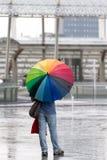 Mann mit Regenbogenregenschirm Stockfotos