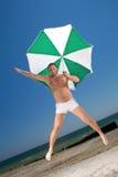 Mann mit Regenschirm auf einem Strand lizenzfreies stockfoto
