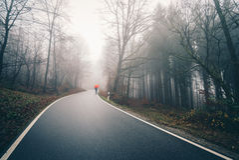 Mann mit Regenschirm auf nebelhaftem Waldweg Lizenzfreies Stockfoto
