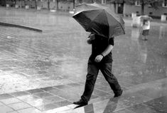 Mann mit Regenschirm im Regen Lizenzfreie Stockfotografie