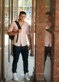 Mann mit Reisetasche auf sonnigem im Freien Macho auf moderne Hemd- und Jeansmode Art und Weisebaumuster auf Straße stattlich stockfotografie