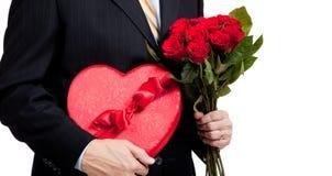 Mann mit Rosen und Inneres mit Schokoladen auf Weiß Stockfotos