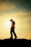 Mann mit roter Kappe auf felsiger Spitze Mann, der über felsigen Gipfel zu Sun geht Schöner Moment das Wunder der Natur Lizenzfreie Stockfotografie
