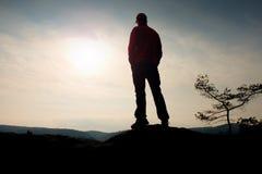 Mann mit roter Kappe auf felsiger Spitze Mann, der über felsigen Gipfel zu Sun geht Schöner Moment das Wunder der Natur Lizenzfreies Stockfoto