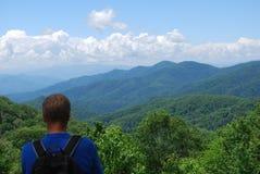 Mann mit Rucksack aufpassend auf die blauen Berge und die Linie von Wolken Lizenzfreie Stockfotografie
