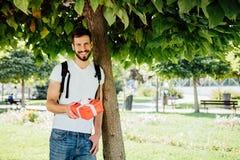 Mann mit Rucksack und einem Geschenk nahe bei einem Baum lizenzfreie stockbilder