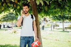 Mann mit Rucksack und einem Geschenk nahe bei einem Baum stockbild