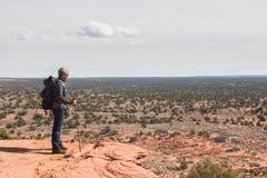 Mann mit Rucksack und Spazierstock am Rand einer Klippe Stockbilder