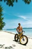 Mann mit Sand-Fahrrad auf Strand Sommer-Reise-Ferien genießend Stockbild