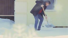 Mann mit sauberem Schnee des Spatens nahe Haus stock footage